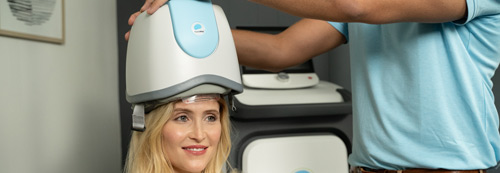Woman sitting in TMS chair for depression treatment.